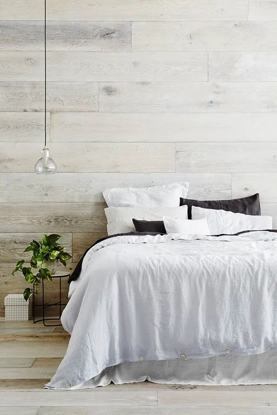 a contemporary yet a bit rustic bedroom with a whitewashed wood headboard wall and a floor, a comfy bed, a pendant lamp and a potted plant