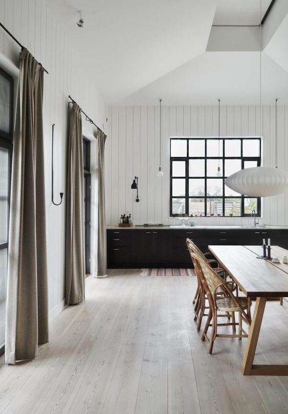 a contrasting kitchen with white walls, black cabinets, whitewashed floors and a lovely wooden dining set