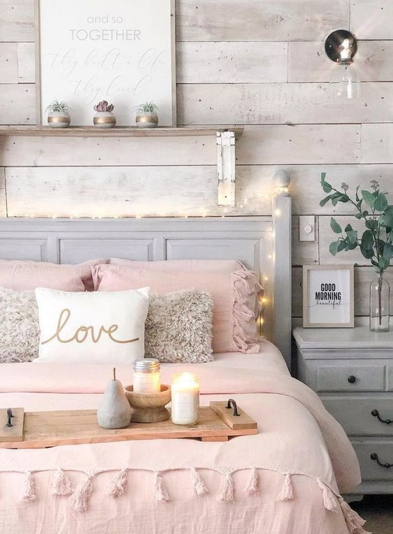a cozy bedroom with a whitewashed wooden accent wall, neutral furniture, lights, a wall sconce, pink bedding and artworks