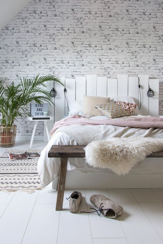 a cozy bedroom with a wooden floor and a whitewashed brick wall, a wooden bed and a bench, catchy bedding and lights