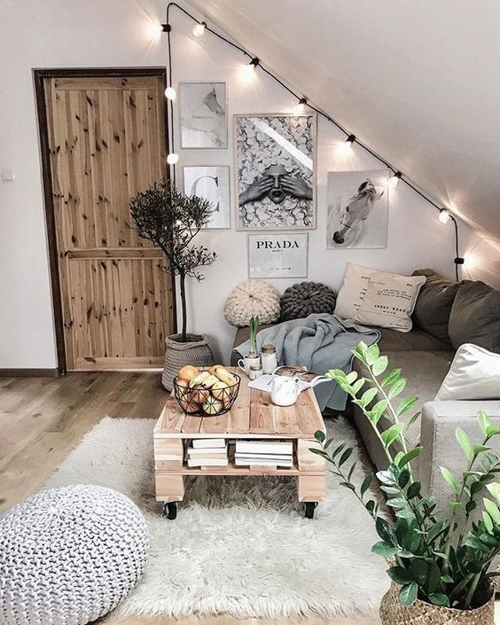 a cozy boho attic living room with a sectional, a pallet table, layered rugs, a gallery wall, string lights and a crochet ottoman