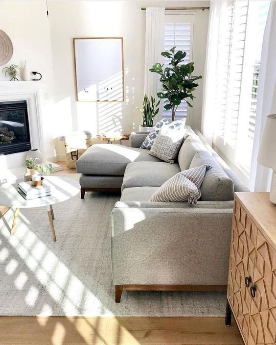 a cozy modern living room with a grey sofa, a built-in fireplace, a round table, potted plants and lots of natural light