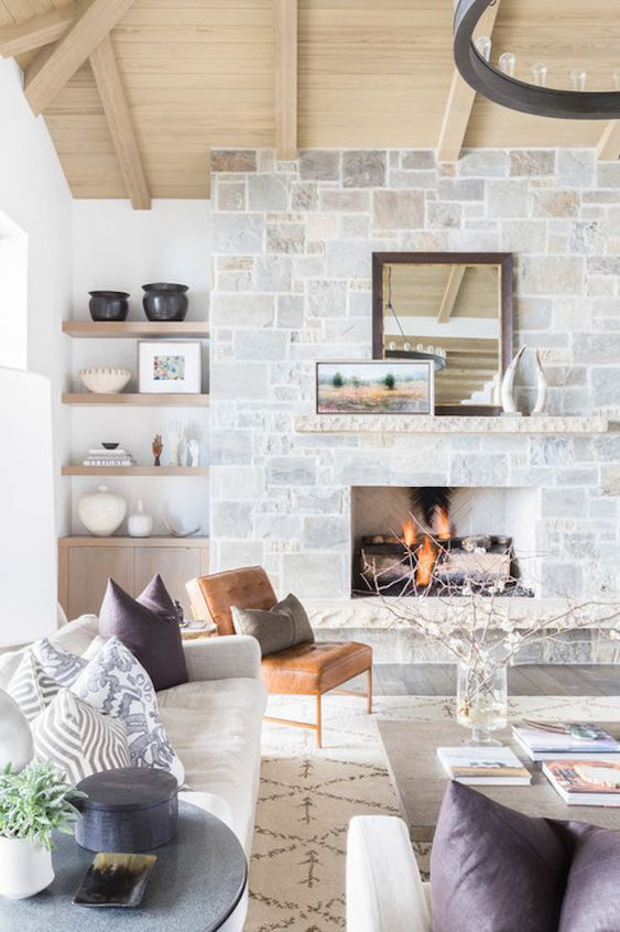 a cozy whitewashed stone fireplace with mantels, vintage decor on the mantel makes the space very wlecoming