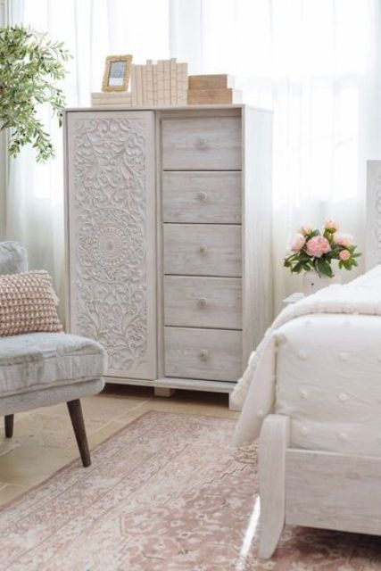 a delicate whitewashed storage unit with five drawers and a beautiful carved door is a lovely solution for a shabby chic bedroom