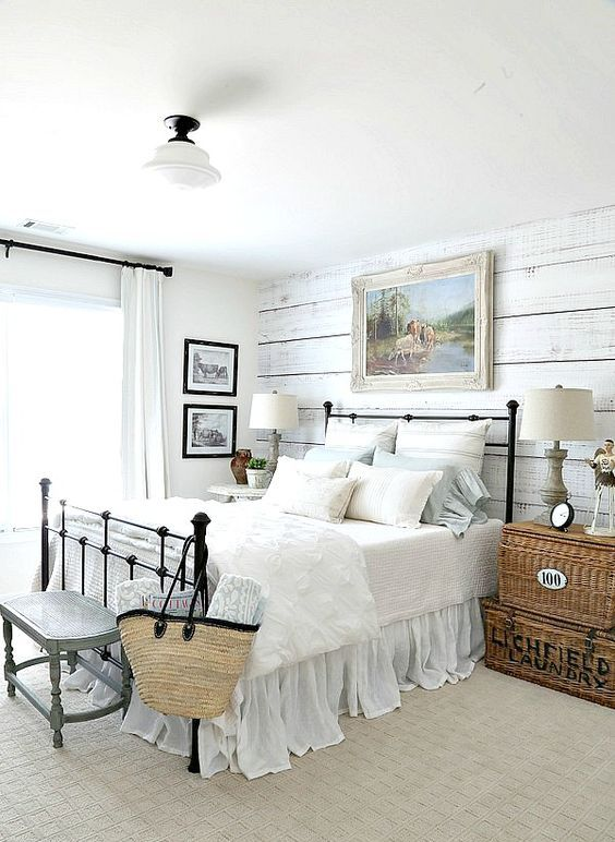 a farmhouse bedorom with a whitewashed wooden wall, a metal bed, stacked woven chests with refined lamps and a rustic artwork