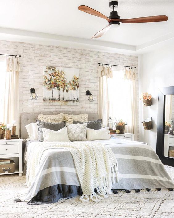 a farmhouse bedroom with a whitewashed brick wall, comfy furniture and a mirror in a large frame is very welcoming