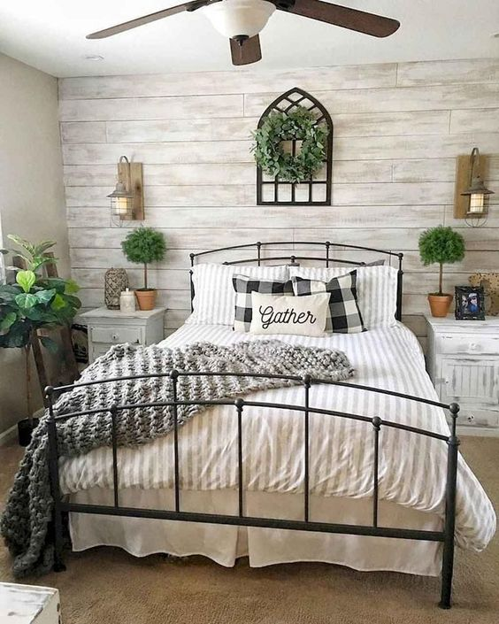 a farmhouse bedroom with a whitewashed wood accent wall, a black metal bed, whitewashed nightstands, potted plants and a greenery wreath