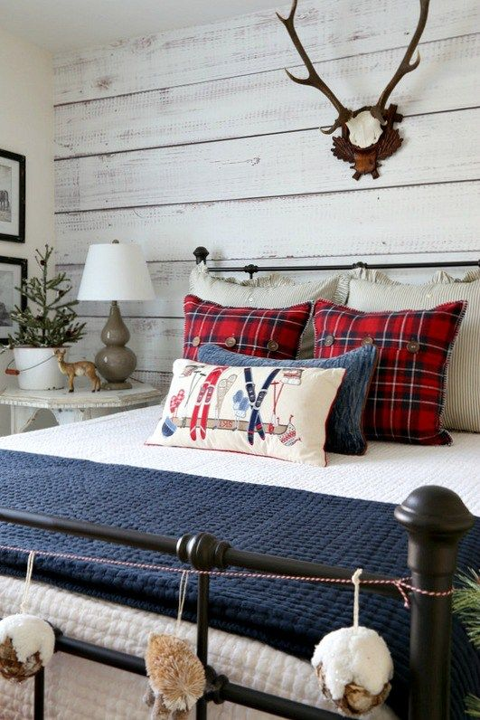 a farmhouse bedroom with a whitewashed wooden wall, a metal bed, whitewashed furniture, bright bedding and antlers on the wall
