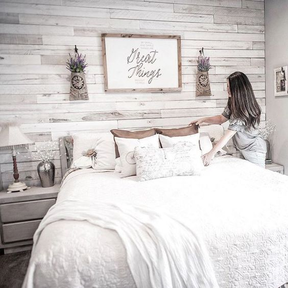 a farmhouse bedroom with a whitewashed wooden wall for an accent, whitewashed furniture, a cozy bed and pendant lavender over the bed