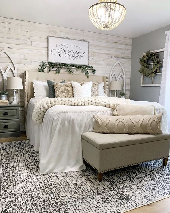 a farmhouse bedroom with a whitewashed wooden wall, neutral upholstered bed and ottoman, vintage nightstands, greenery and a vintage chandelier