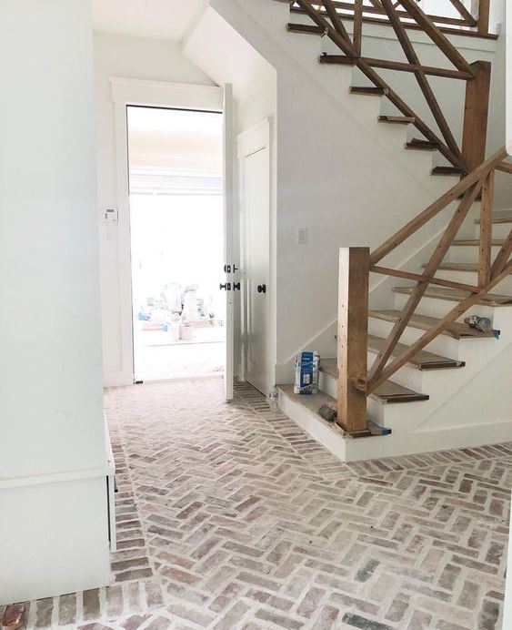 a farmhouse foyer with a whitewashed brick floor and a wooden staircase is lovely and welcoming