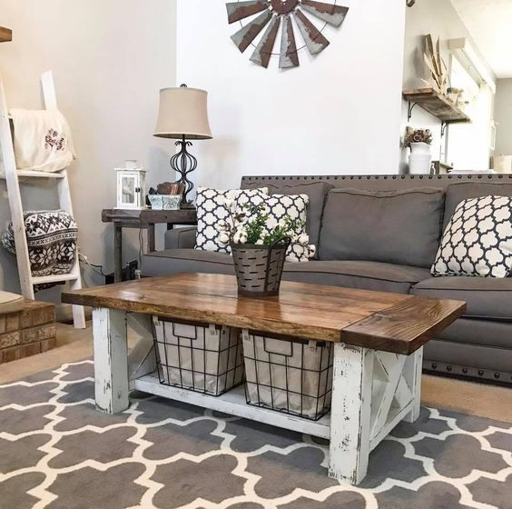 a farmhouse living room with a graphite grey sofa, a ladder for hanging stuff, a whitewashed and stained coffee table, printed textiles is all cool