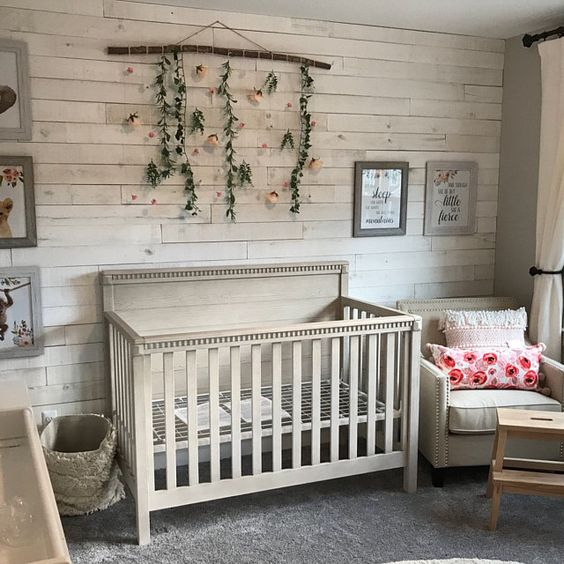 a farmhouse nursery with a whitewashed wooden wall, vintage tan furniture, a floral pendant and artworks is super cool
