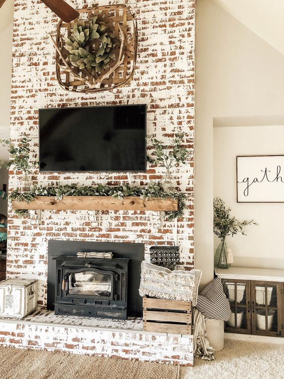 a farmhouse shabby chic fireplace with a wooden mantel covered with greenery, a woven basket and antlers