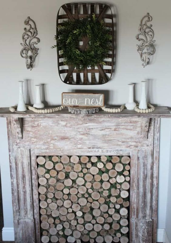 a faux shabby whitewashed wooden fireplace with wood slices in it and some rustic decor is chic