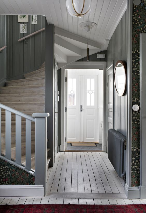 a grey farmhouse entryway with grey walls, a whitewashed floor, a wooden staircase and doors painted white