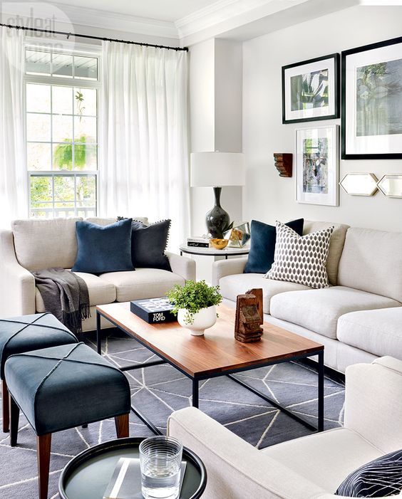 a lively living room with white furniture, navy stools, a wooden table, a printed rug, printed pillows and airy curtains