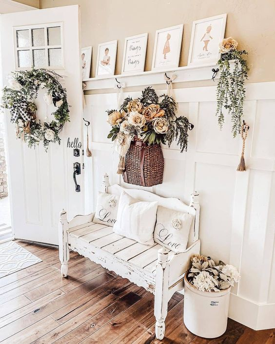 a lovely farmhouse entryway with white paneling, a whitewashed and distressed bench, faux bloom and greenery decor and a pretty vintage gallery wall