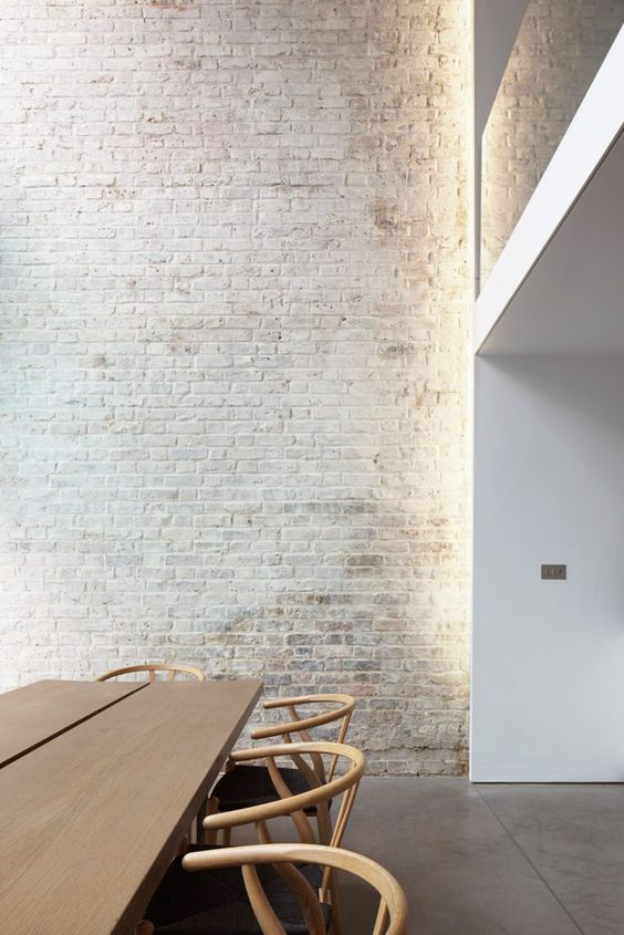 a minimalist dining room with a whitewashed brick wall that brings more interest and catchiness to the space