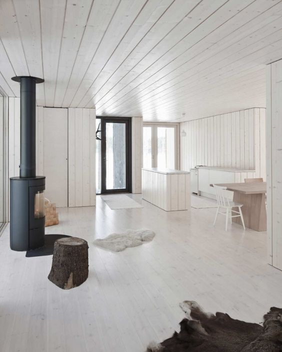 a minimalist space with whitewashed walls, a ceiling, a floor and wooden furniture and a hearth