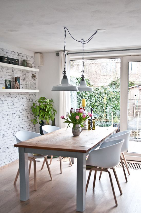 a modern Nordic dining room with a whitewashed brick wlal, a modern dining set and vintage lamps and potted plants