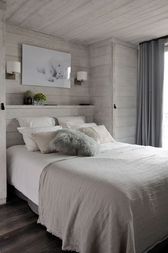a modern bedroom with whitewashed wooden walls, sconces, an artwork and neutral layered bedding is very cozy