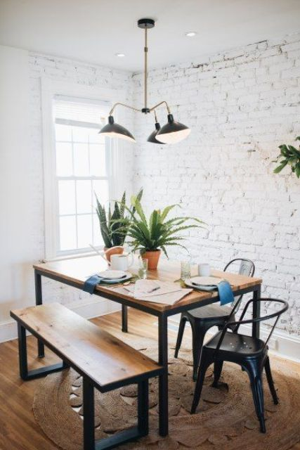 a modern dining zone with whitewashed brick walls, a chic dining set and metal chairs and a retro chandelier