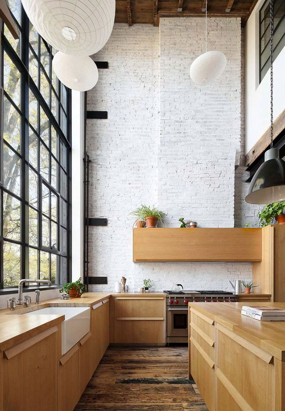 a modern double-height kitchen with whitewashed brick walls, sleek wooden cabinetry, pendant lamps and potted greenery