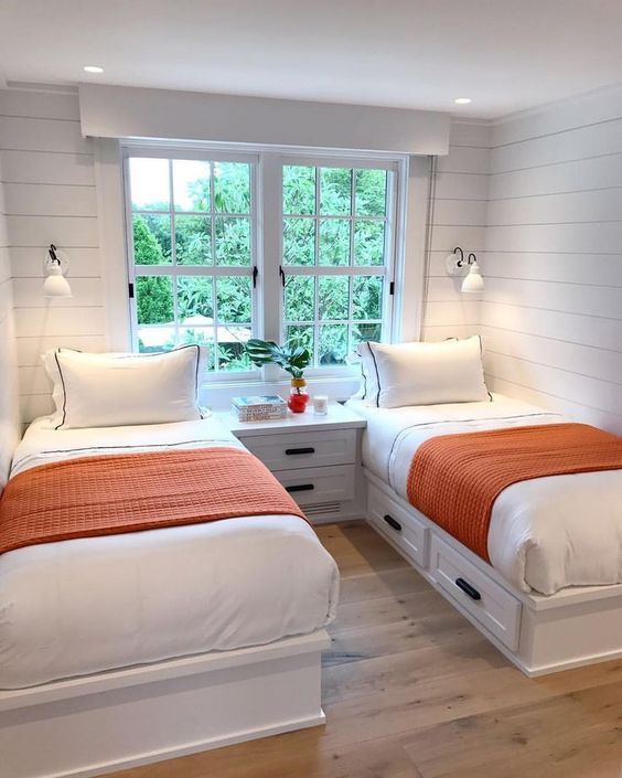 a modern farmhouse guest bedroom with whitewashed wooden walls, neutral furniture, wall sconces and a large window