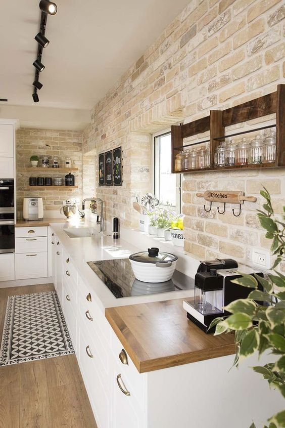 a modern farmhouse kitchen with whitewashed brick walls, sleek white cabinets is a very elegant and cool