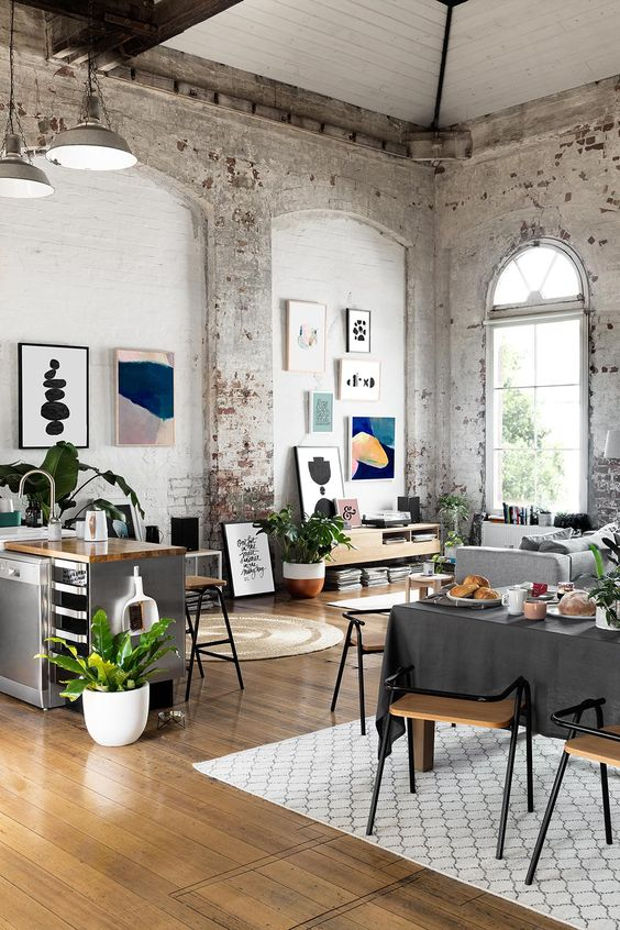 a modern loft-like layout with whitewashed shabby chic brick walls, stylish modern furniture, pendant lamps and bright artworks