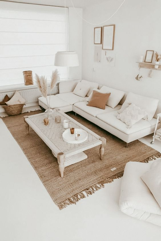 a neutral boho living room with a white sectional, a woven table, a jute rug, pampas grass, a gallery wall and lots of pillows