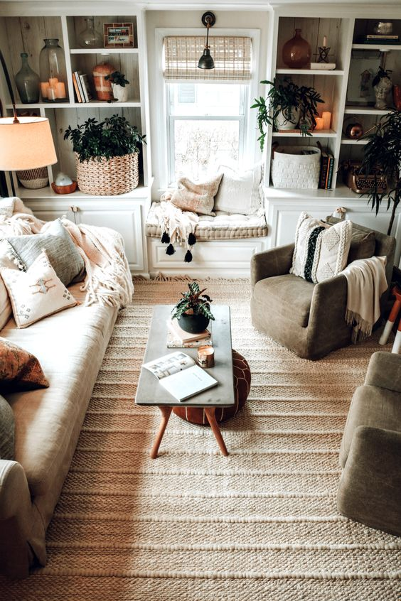 a neutral boho living room with lots of texture, potted greenery, a sofa, chairs and a window seat plus a leather ottoman
