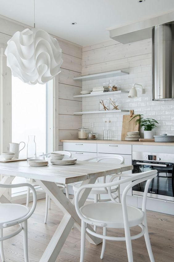 a neutral eat in kitchen is made catchier with a whitewashed wooden wall, a white tile backsplash and a white dining set plus a ruffle lamp