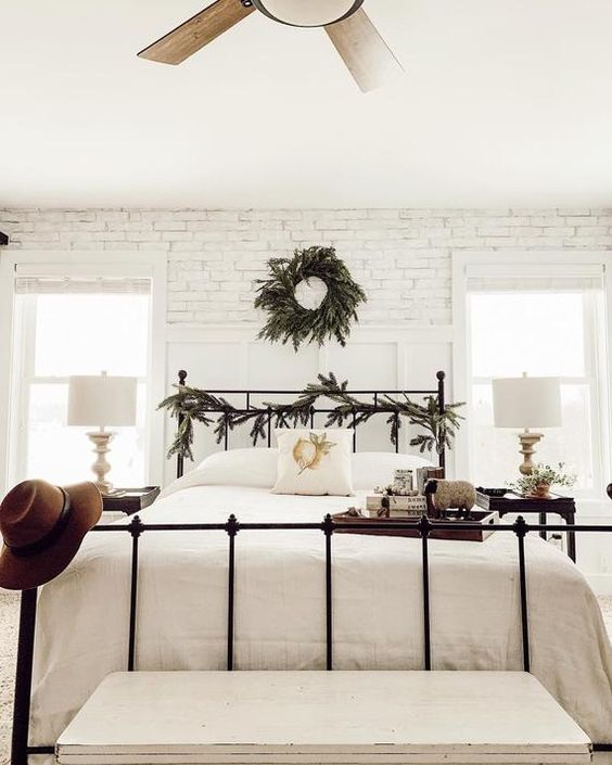 a neutral farmhouse bedroom with whitewashed brick walls, a forged bed, dark nightstands and neutral bedding