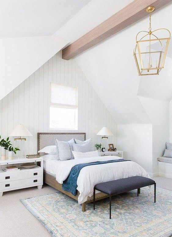 a neutral farmhouse bedroom with whitewashed wooden walls, chic furniture, a wooden beam, a vintage lamp on it and blue bedding
