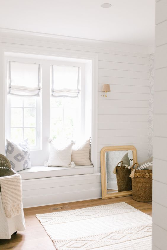 a neutral farmhouse entryway with whitewashed wooden walls, a daybed on the windowsill and pillows and baskets