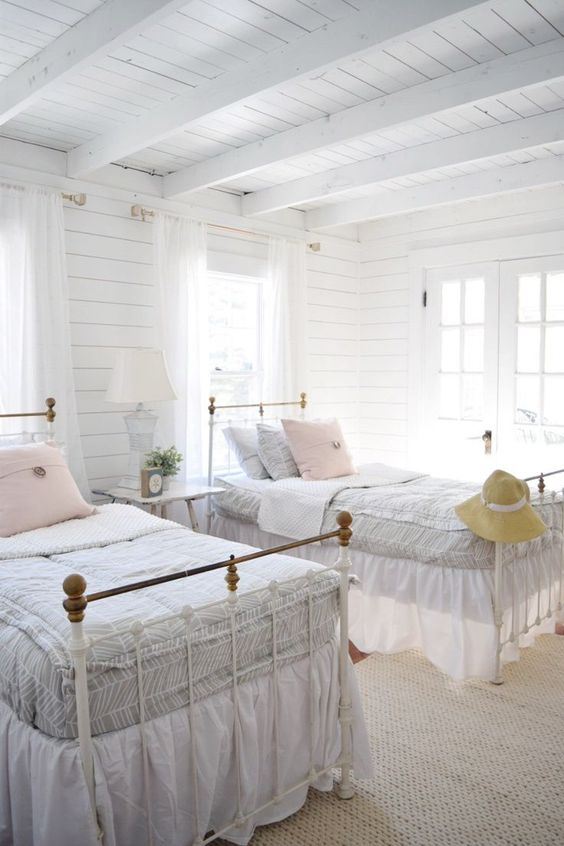 a neutral farmhouse guest bedroom with whitewashed wooden walls and a ceiling, refined vintage beds and a stool with a table lamp