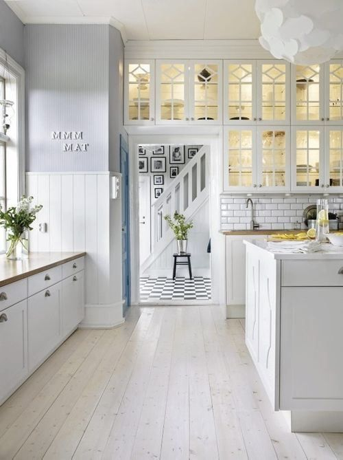 a neutral farmhouse kitchen with paneled walls, whitewashed floors, white cabinets and a white subway tile backsplash