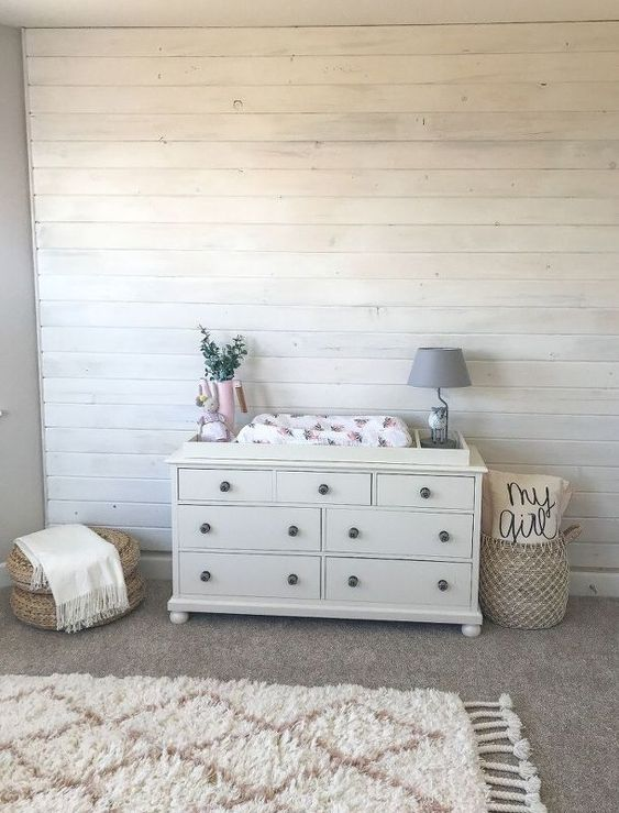 a neutral farmhouse nursery doe with whitewashed wooden walls, a printed linens, a basket with various stuff is a cool space