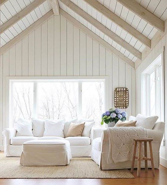 a neutral living room with whitewashed wooden wall and a ceiling, white furniture, some wooden stools and blooms