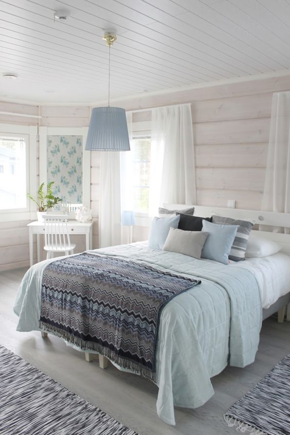 a neutral rustic bedroom with whitewashed wooden walls, simple and chic furniture, blue and grey bedding and a blue pendant lamp, a vanity corner with a mirror