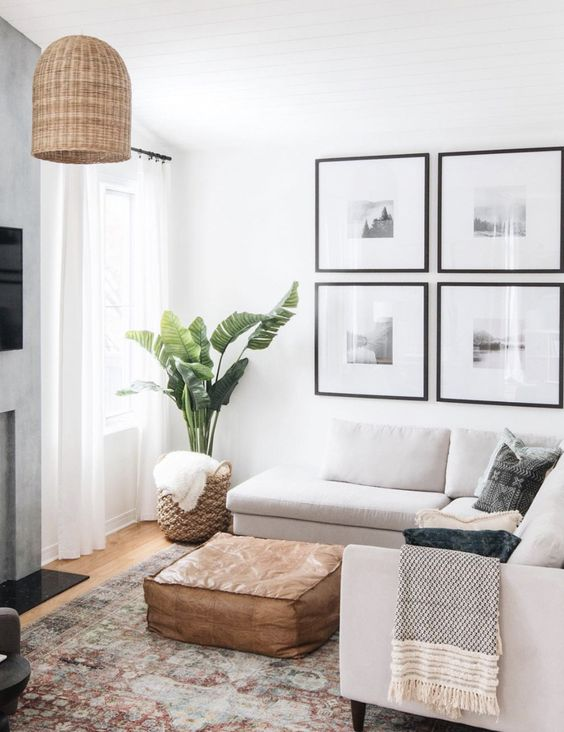 a neutral small living room with a sectional, a leather ottoman, a gallery wall, a woven lamp and a potted plant