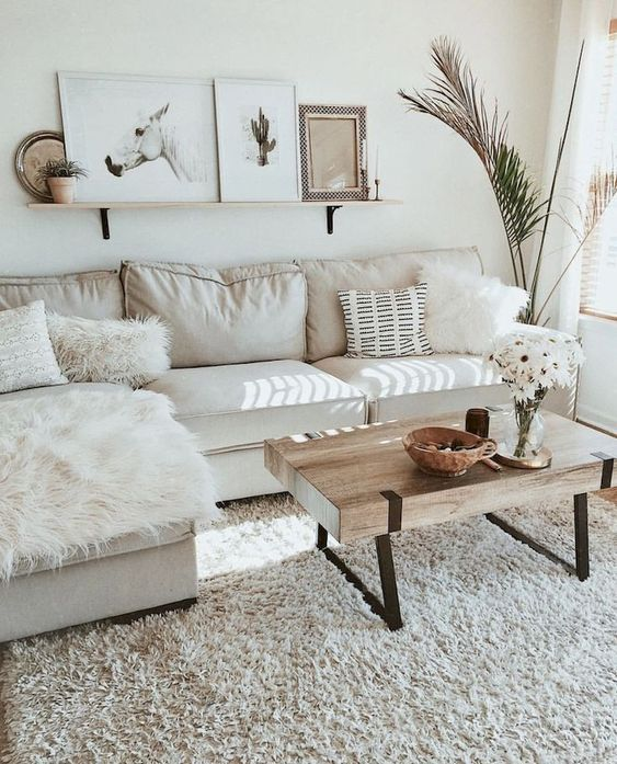 a neutral small living room with a sectional sofa, a wooden table, lots of fur pillows and a gallery wall on a shelf