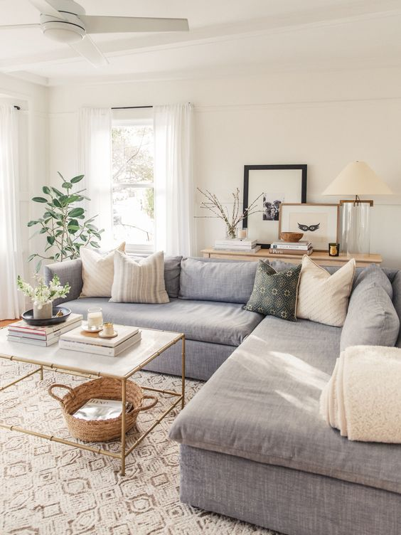 a peaceful small living room with a grey sectional, printed pillows, some plants, a gold table and printed rugs