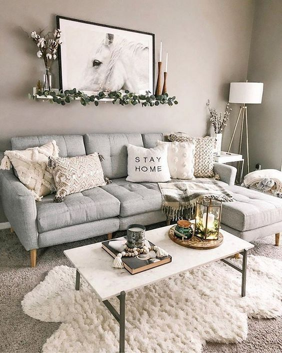 a pretty boho living room with a grey sofa, a white table, layered rugs, neutral tables, some candles and an artwork