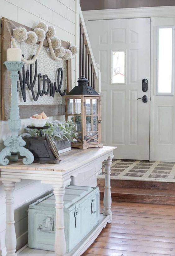 a pretty farmhouse entryway with a whitewashed vintage console table, a blue chest for storage, a candle lantern, a blue candleholder and some beautiful decor