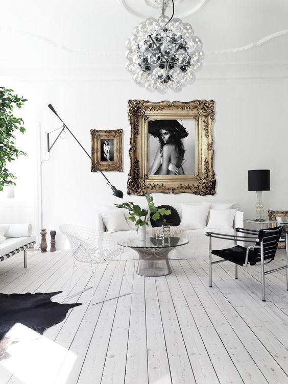a refined and chic living room with white walls, a whitewashed floor, black and white furniture and refined artworks