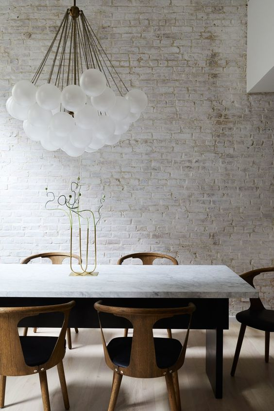a refined modern dining room with a whitewashed brick walls, a marble table, modern chairs and a cluster of bulbs