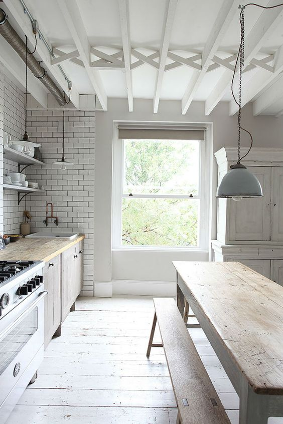 a relaxed Nordic kitchen with white subway tiles, a whitewashed wooden floor and wooden furniture plus pendant lamps